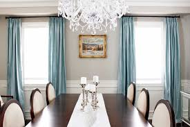 grande chandelier with soft blue curtain and white chairs for