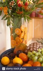 arrangement fruit bowl of fruit beside arrangement of flowers in glass