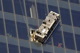 window washers trapped on scaffolding dangling from one world