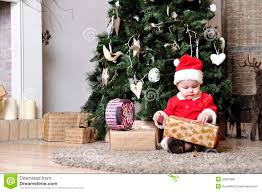 baby in santa costume sit near decorating christmas tree and try