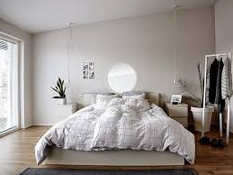 minimalist bedroom with white walls and bedding also hanging bulb
