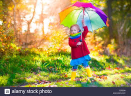 little playing in the rain in autumn park child holding