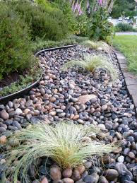 polished black river rock with small plants with stone border with