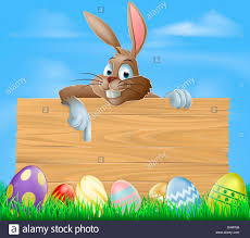 cartoon easter bunny pointing at blank wooden sign with painted