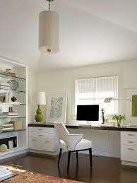 white office with dark floors large desk under window and glass