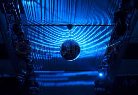 ball with light inside silhouette disco ball hanging at ceiling reflected with blue lights