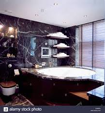bathtub edging marble edging on large circular bath in black marble bathroom with