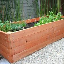 wooden tubs for garden beside a bench on the front porch add a