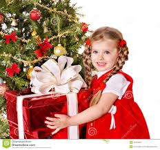 child giving gift box by christmas tree royalty free stock