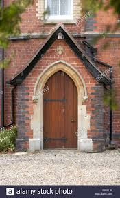 gothic victorian porch and door in red brick house stock photo