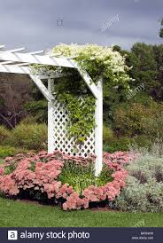 a white lattice arbor with abundant flowers and climbing plants in