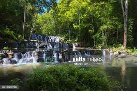beautiful green color of water at three tiered waterfall stock