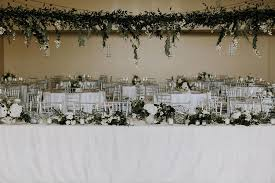 discovery gardens wedding wedding table with hanging organic greenery installation