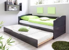 dark gray stained wooden trundle daybed with white and green
