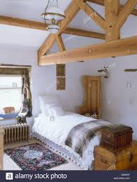 wooden apex beams in country loft conversion bedroom with white