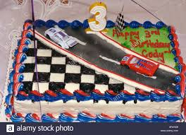 boys birthday race car cake waiting to be lit at 3 year boys birthday party