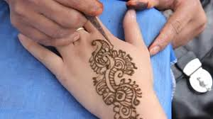 an indian lady does a henna tattoo on a client u0027s fingers and hand