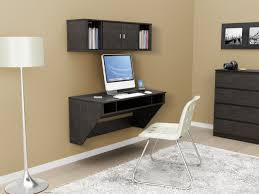 black wood wall mounted bookshelf over computer desk with storage for saving small home office spaces plus white leather chair with stainless steel base
