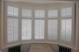 bay window wooden plantation shutters in full height with our 63mm