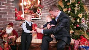 father gives a christmas gift sons children watching gifts from