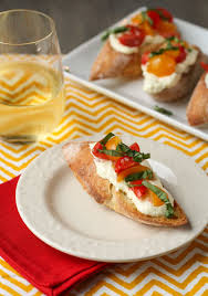 crostini with whipped feta and tomatoes garnish with lemon