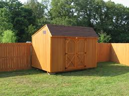 wooden cedar stained quaker style shed along backyard fence