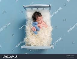 baby cuddling his favorite blue toy stock photo 579571393