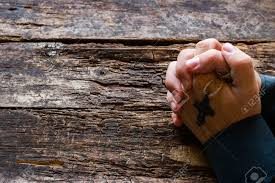 praying with a cross in his on the wooden background