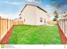 house fenced back yard exterior with well kept lawn stock photo