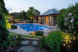 low voltage lighting near swimming pool lush plantings around the pool and pool house form a natural