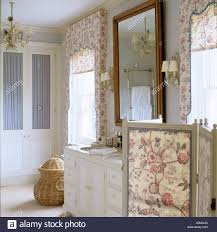 floral patterned blinds and dressing screen in bathroom of english