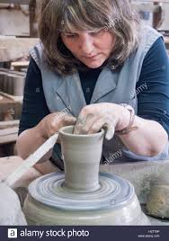 throwing a pot throwing a pot on a pottery wheel a craftswoman raises the edges of