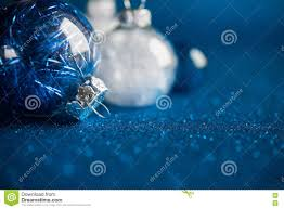 white and blue ornaments on blue glitter background