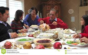 grandfather carving turkey at family thanksgiving meal stock