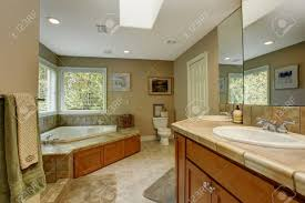 spacious bathroom with tile wall trim and corner bath tub view