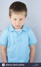 sad and forlorn 5 year boy with a light blue shirt looking at