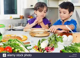 2 indian kids boy and kitchen cooking preparation stock photo
