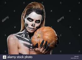 halloween black background pumpkin woman with skeleton halloween makeup holding pumpkin over black