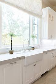 what is a shade of white for kitchen cabinets a white and light gray shade hangs from a window above