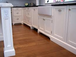 closeup of light rail skirt trim on painted linen shaker cabinets