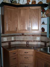 dark countertop with cream tan tile backsplash and double copper