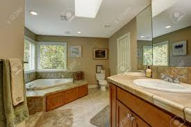 Corner Bathroom Vanities And Cabinets by Spacious Bathroom With Tile Wall Trim And Corner Bath Tub View