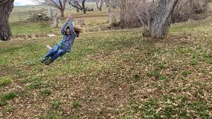 a tween spins on a tree swing motion stock footage