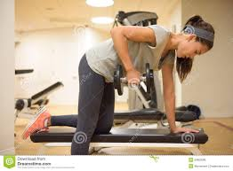fitness gym woman strength training lifting weights stock photo