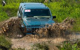mud jeep cherokee off road vehicle brand jeep cherokee overcomes a pit of mud