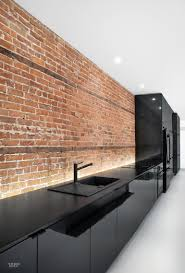 long and lean k b stars in montreal apartment renovation lets kitchen cabinetry clad in plastic laminate hugs the apartment s original brick wall photography by adrien williams