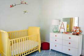 nursery room with white dresser with accessories and yellow crib
