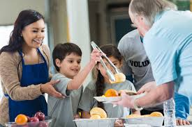 homeschooling young hispanic family volunteering to serve food in soup kitchen