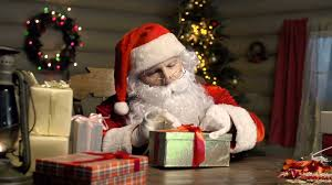 close up of santa claus packing gifts in beautiful boxes with care