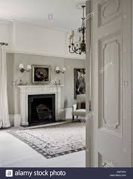 view through a panelled door into elegant bedroom painted in pale